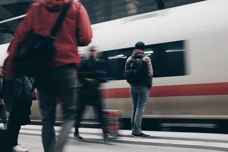 Menschen auf einem Bahngleis während ein Zug einfährt.