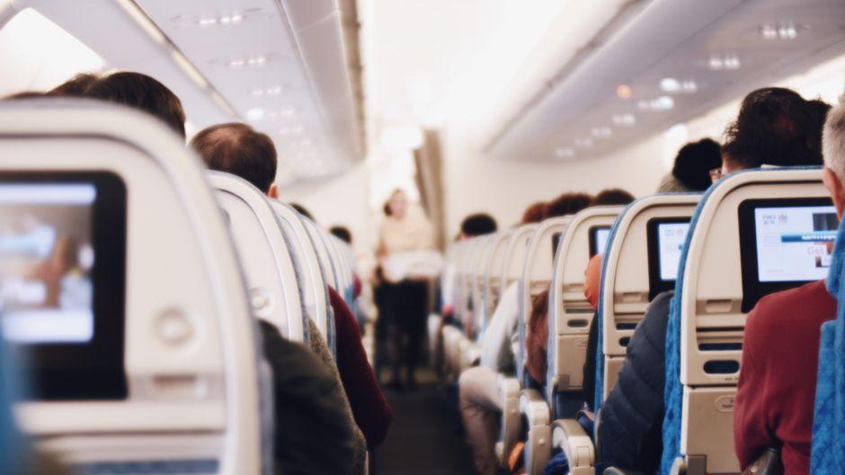 Fluggäste in einer Flugzeugkabine.