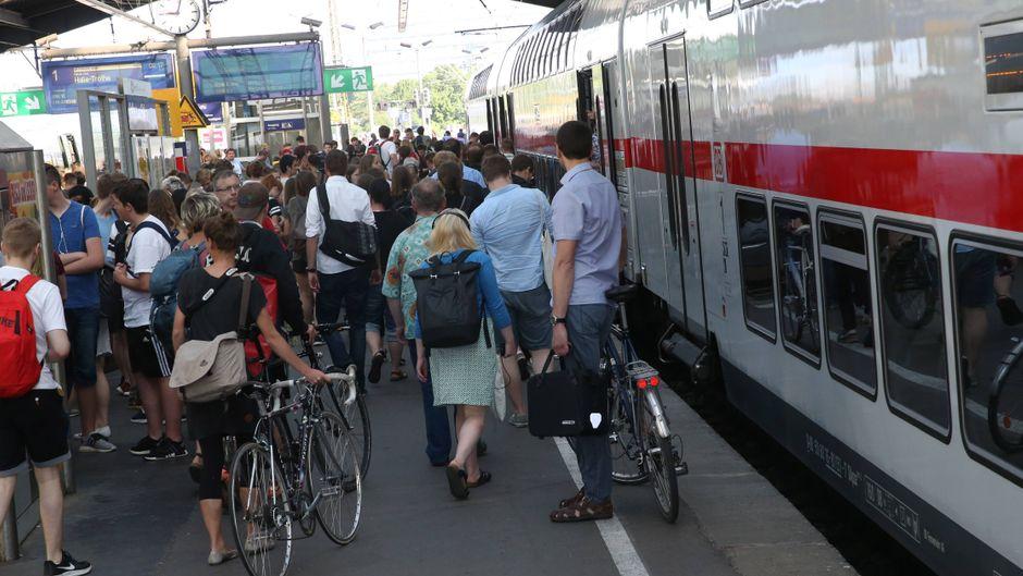 Fahrgäste verlassen und besteigen einen Zug am Leipziger Bahnhof.