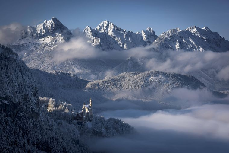 Schloss Neuschwanstein thront vor den Allgäuer Alpen in der bayerischen Schneelandschaft.