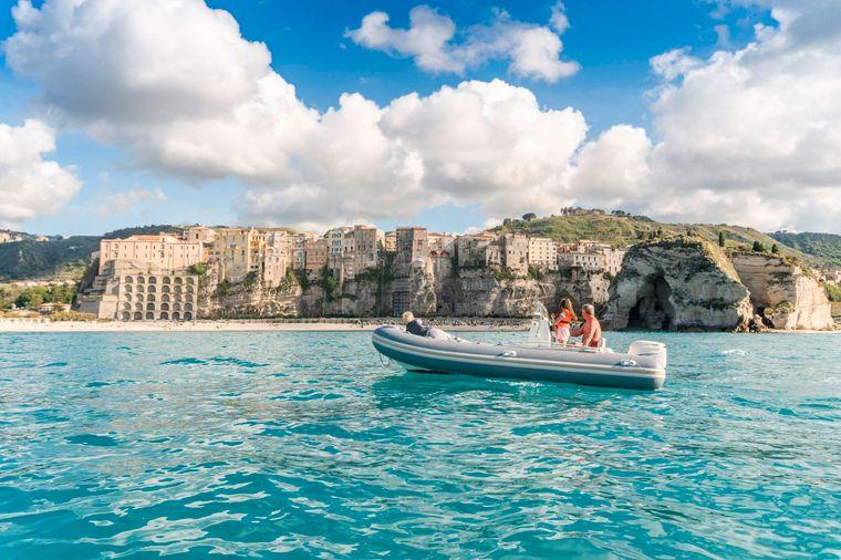 Ein Motorboot fährt vor der Küste von Tropea entlang.