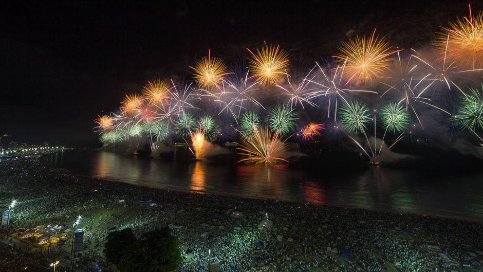 Tausende Menschen tanzen am Strand der Copacabana beim Silvesterfeuerwerk.