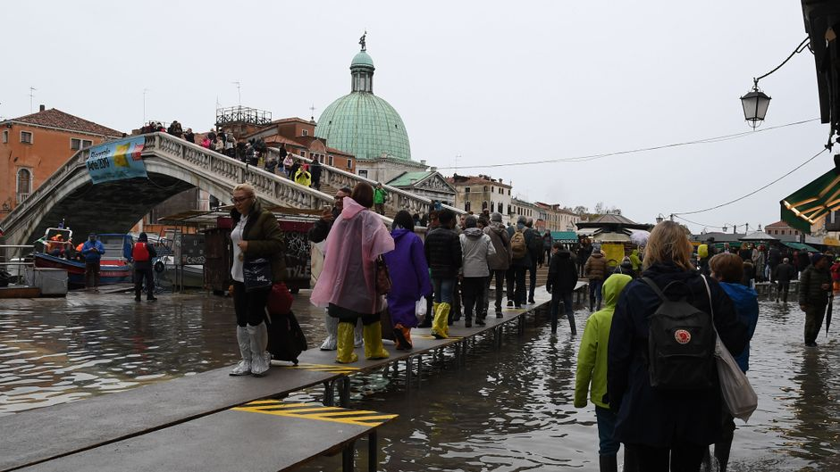 Menschen bahnen sich ihren Weg durch die unter Wasser stehende Innenstadt von Venedig.