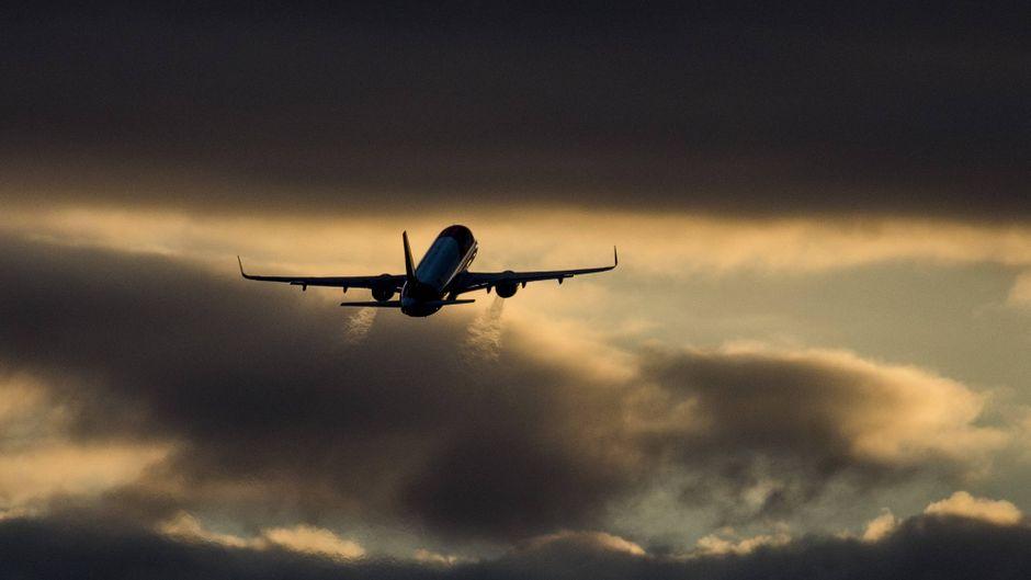 Ein Flugzeug startet während des Sonnenuntergangs.