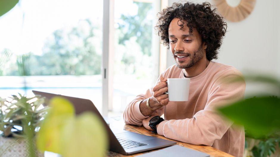 """Ein Mann sitzt am Laptop (Symbolbild). Das Online-Portal """"Der Reisemanager"""" verspricht Hilfe bei der Urlaubsplanung in Zeiten von Corona."""