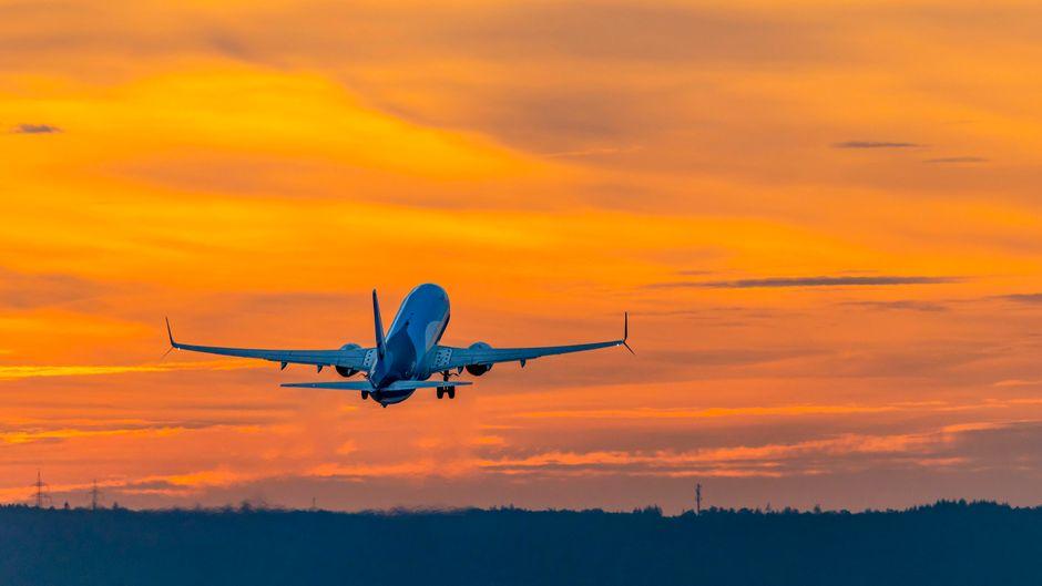Ein Flugzeug fliegt dem Sonnenaufgang entgegen.