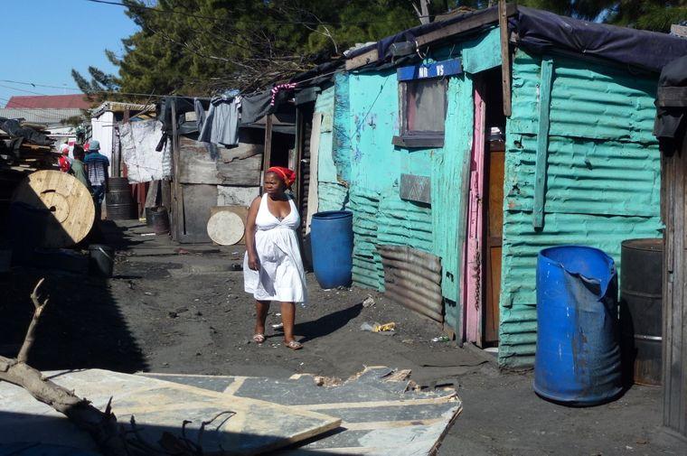 Eine Frau vor Elendshütten im Township Langa in Kapstadt.