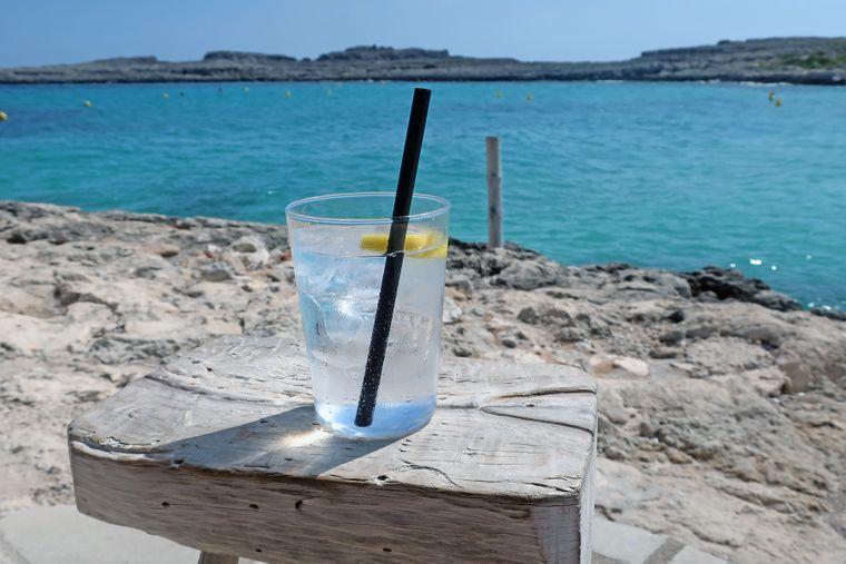 Ein Glas mit Gin Tonic vor dem Meer auf Menorca, Balearen.