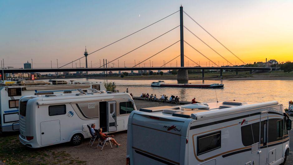 Camping-Urlaub in Deutschland kann so schön sein – Sonnenuntergang über dem Düsseldorfer Campingplatz am Rheinufer.