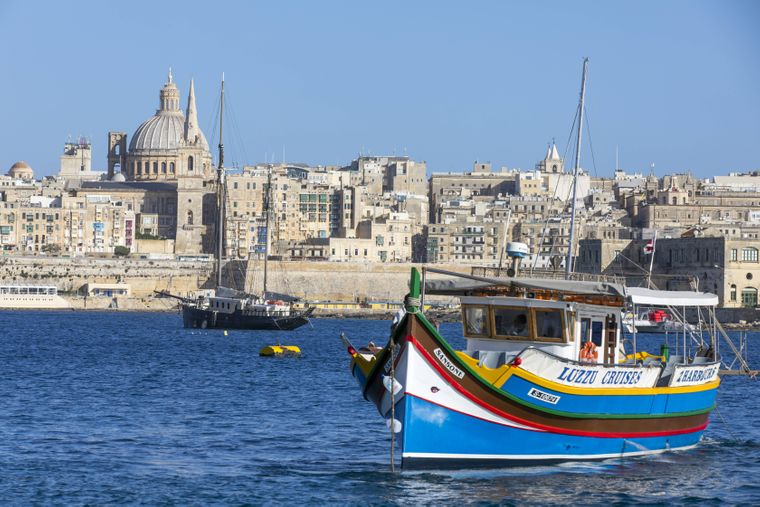 Skyline von Valletta, der Hauptstadt von Malta, Kuppel der Karmelitenkirche und Kirchturm der St. Paul's Anglican Pro-Cathedral und ein maltesisches Fischerboot.