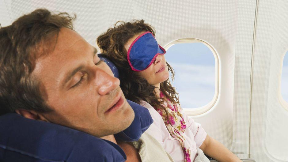 Zwei Menschen machen im Flieger ein Nickerchen.