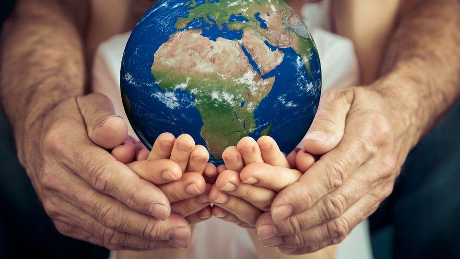 Ein Kind hält einen Globus in der Hand. Wie schreiben sich die Hauptstädte der Welt richtig?