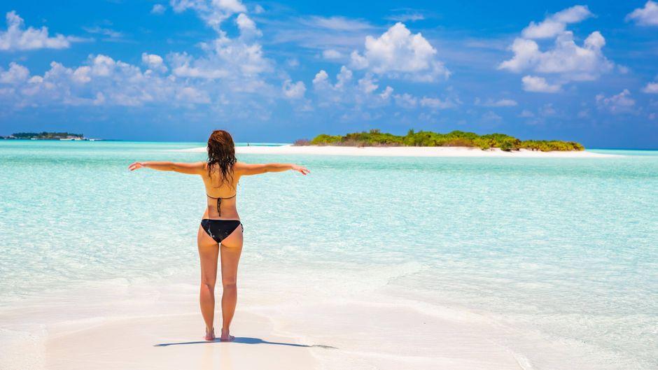 Eine Frau im Bikini steht mit ausgebreiteten Armen auf einem weißen Sandstrand auf den Malediven.
