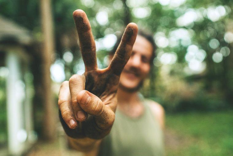 Ein Mann zeigt mit zwei Fingern das Peace-Zeichen