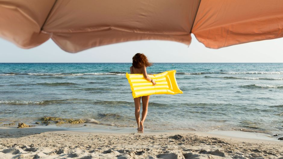 Young woman with yellow airbed at the beach model released Symbolfoto PUBLICATIONxINxGERxSUIxAUTxHUNxONLY JPTF00257imago images/Westend61