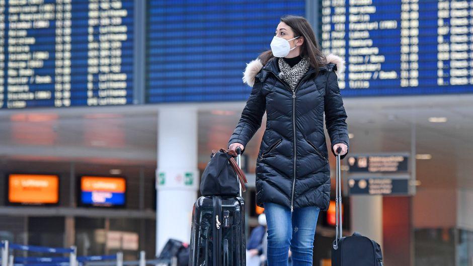 Frau mit Maske am Flughafen München. Ob sich Reiserückkehrer vor Einreise auf Corona testen lassen müssen, hängt von der Art des Risikogebietes ab.