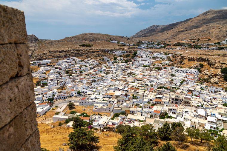 Die Stadt Lindos erstreckt sich mit ihren markanten weißen Häusern über die Landfläche.