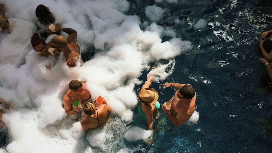 Männer und Frauen auf einer Schaumparty im Pool.