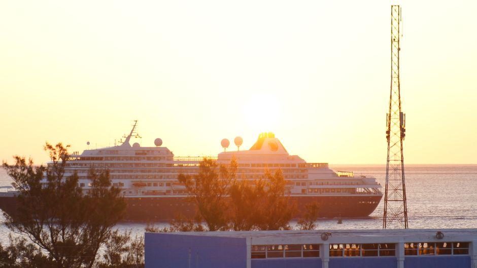 Ein Kreuzfahrtschiff fährt in Richtung Sonnenuntergang.