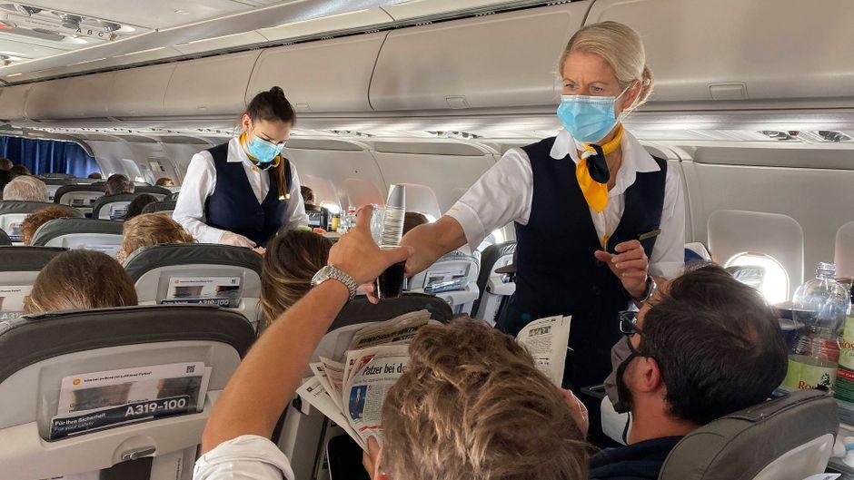 Crewmitglieder mit Mund-Nasen-Schutz bedienen Fluggäste an Bord einer Lufthansa-Maschine.
