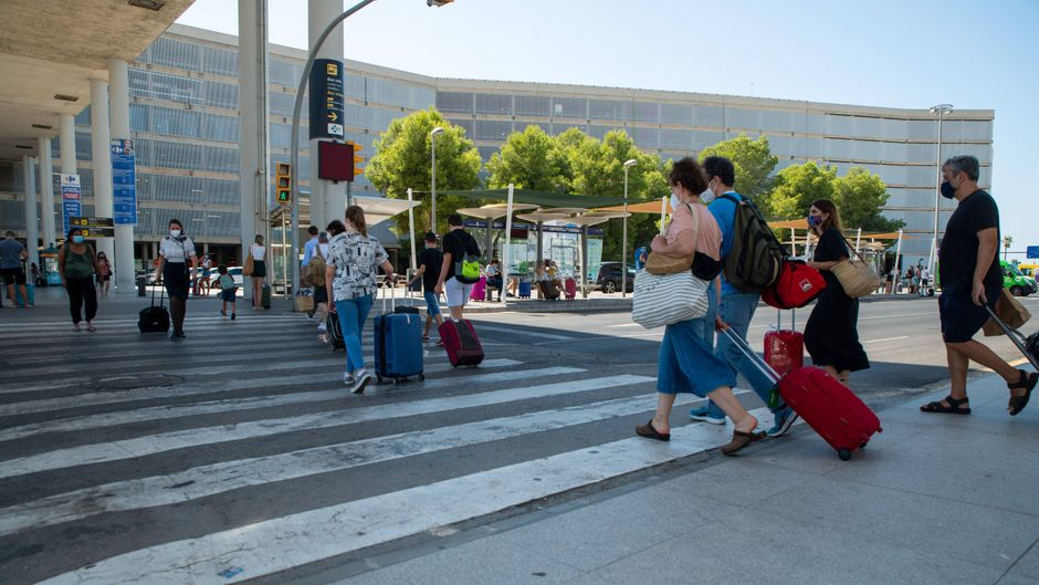 Touristen mit Mundschutz am Flughafen Palma de Mallorca.