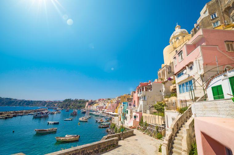 Fischerboote im türkisblauen Meer und bunte Gebäude – Wohnhäuser, Restaurants und Cafés – in Marina Corricella.