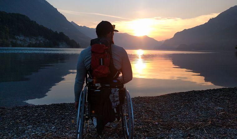 Eamon steht an einem See und blickt in den Sonnenuntergang.