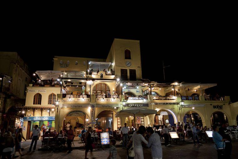 Straßencafés und kleine Läden am Platia Ippokratou bei Nacht in der Altstadt von Rhodos.