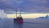 Eisberg in Grönland in Abendstimmung mit Schiff