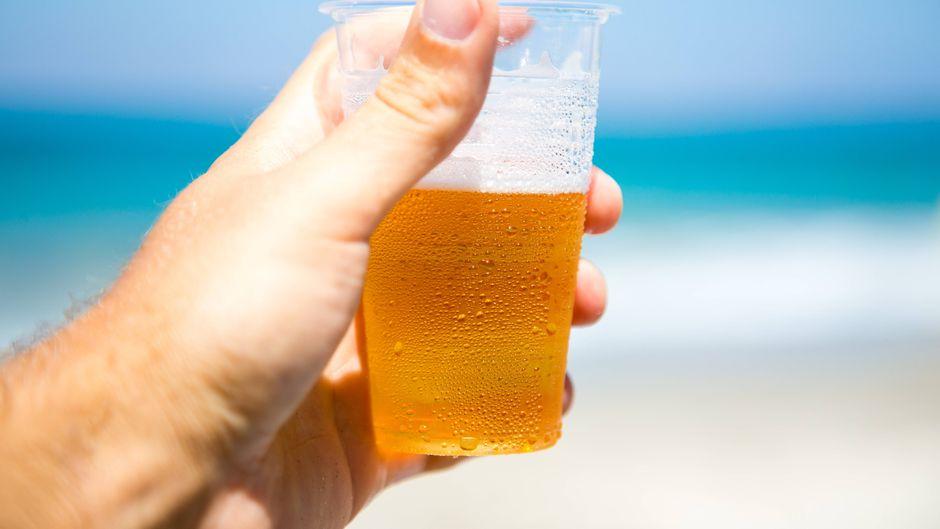 Ein Bier im Plastikbecher am Strand.