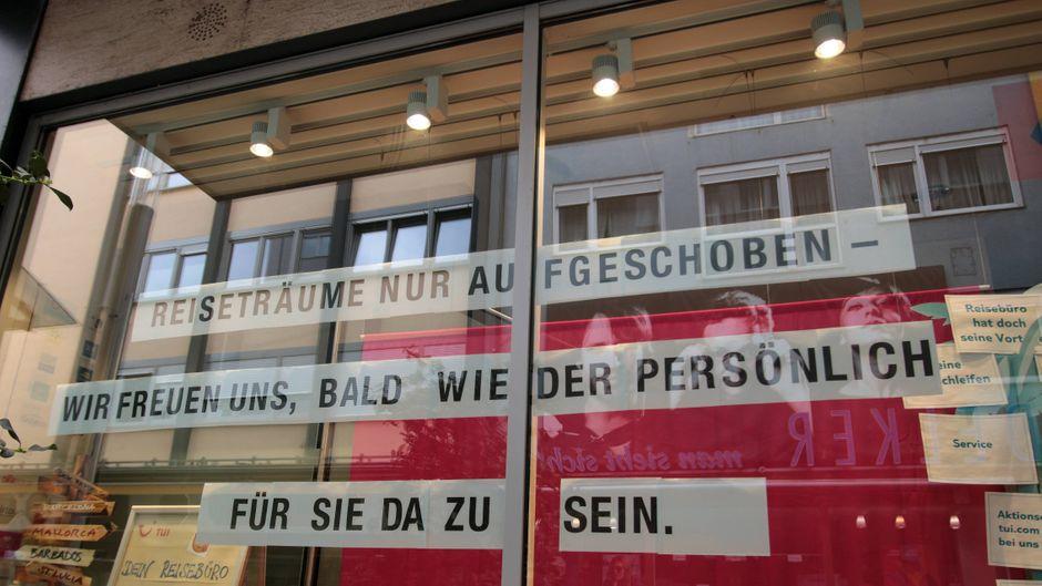 """Schriftzug """"Reiseträume nur aufgeschoben – wir freuen uns, bald wieder persönlich für Sie da zu sein"""" im Schaufenster eines geschlossenen Tui-Reisebüros in der Innenstadt von Mannheim."""