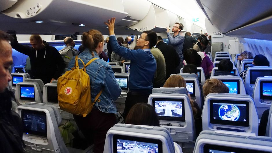 Menschen im Flugzeug verstauen vor dem Abflug ihr Handgepäck.