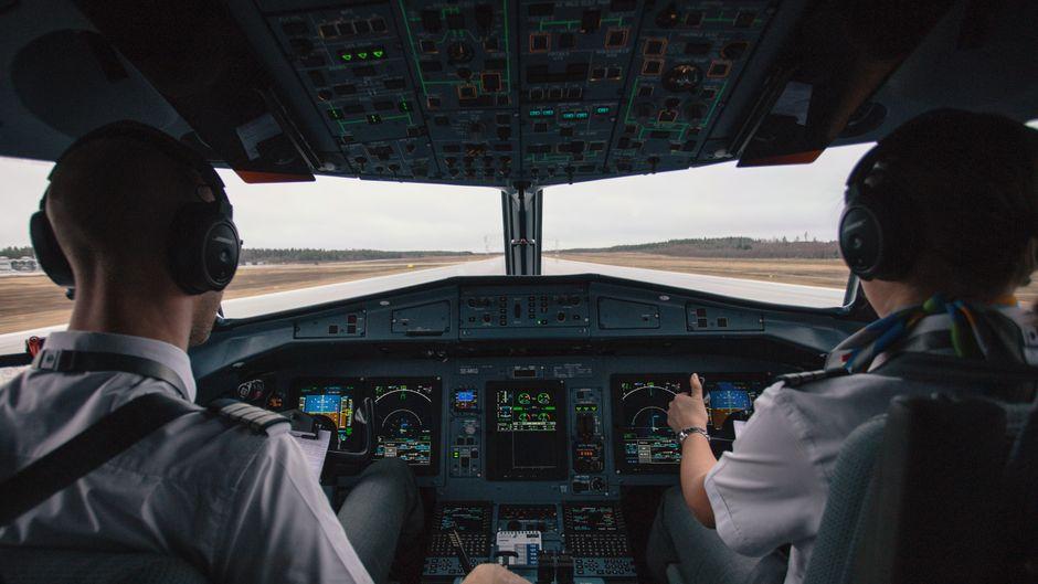 Zwei Piloten sitzen im Cockpit und landen ein Flugzeug am Flughafen.