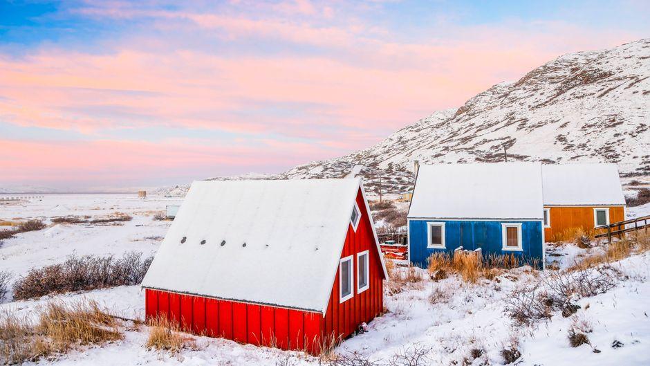 Bunte Holzhäuser im Schnee auf Grönland.