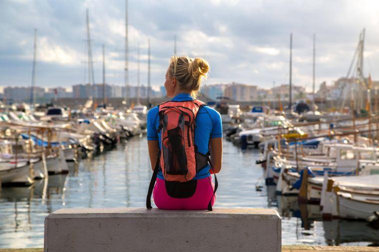 Eine Frau mit Rucksack sitzt am Hafen.
