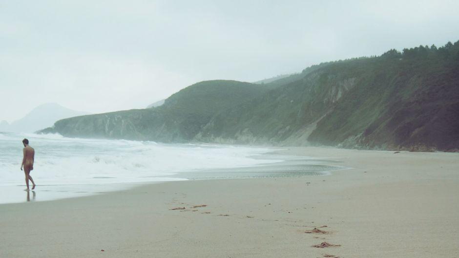 Ein Mann läuft nackt ins Meer.
