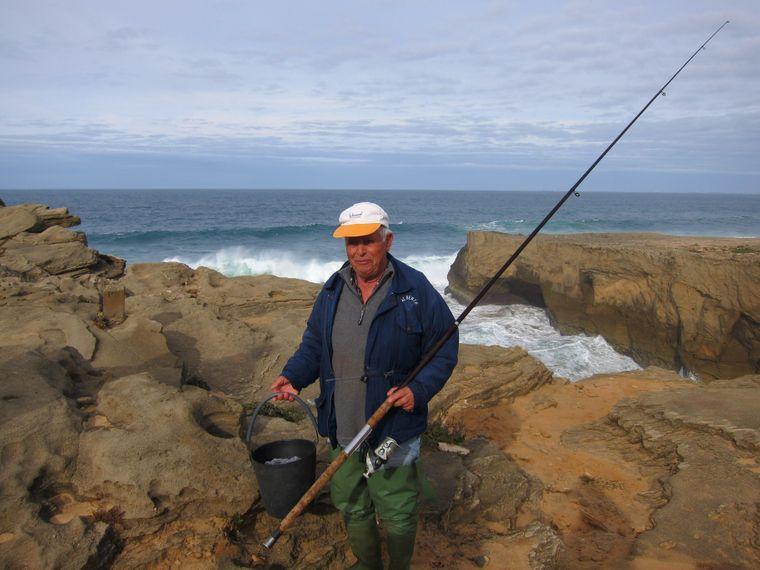 Antonio Silva aus Brunheiras angelt von einem Felsen der Steilküste aus Barsche.