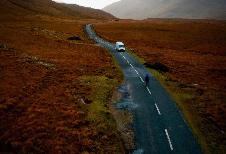 Ein Mensch und ein Van stehen einsam auf einer Landstraße in Irland.
