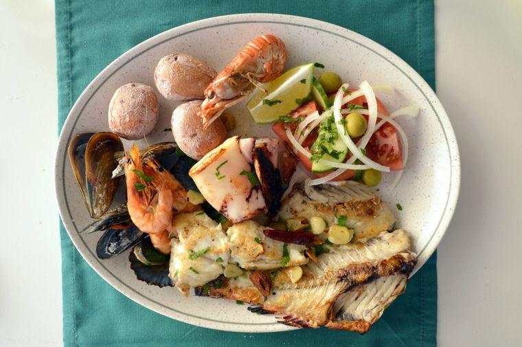 Landestypischer Fischteller mit Garnelen, Muscheln, Weißfisch, Tintenfisch, Salzkartoffeln.