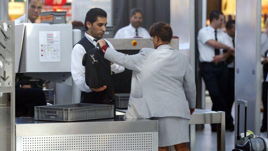 Reisende übergibt dem Angestellten des Sicherheitsdienstes ein Gepäckstück für die Untersuchung im Röntgengerät am Flughafen Köln/Bonn.