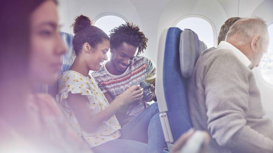 Ein junges Paar sitzt im Flugzeug und schaut Fotos auf einer Kamera an.