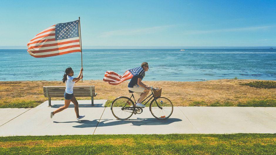 Eine junge Frau und ein junger Mann tragen US-Flaggen.