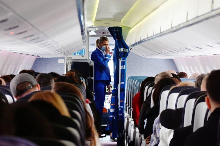 Eine Flugbegleiterin und Passagiere tragen Masken an Bord eines Flugzeugs.