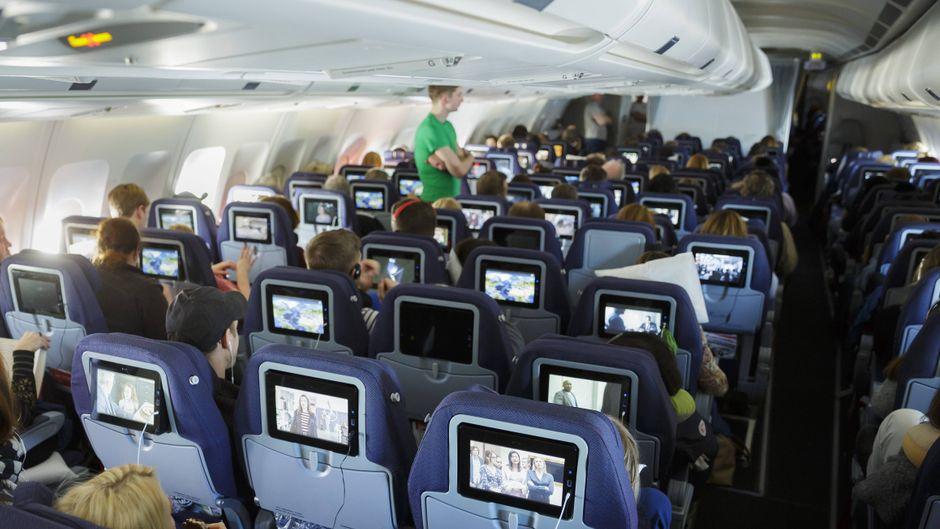 Passagiere schauen das Unterhaltungsprogramm im Economyclass-Bereich in einem Flugzeug.