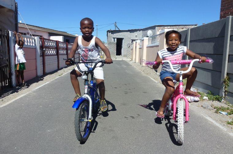 Zwei Kinder im Township Langa in Kapstadt präsentieren voller Stolz ihre Fahrräder.