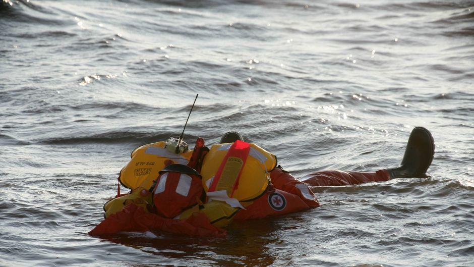 Besatzungsmitglied des Seenotrettungskreuzers Hermann Rudolf Meyer übt im Schutzanzug das Manöver Mann über Bord in der Nordsee.