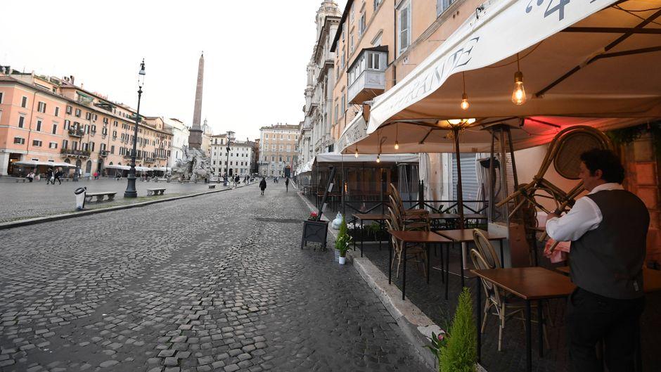 Der Mitarbeiter eines Restaurants in Rom räumt Tische und Stühle rein.
