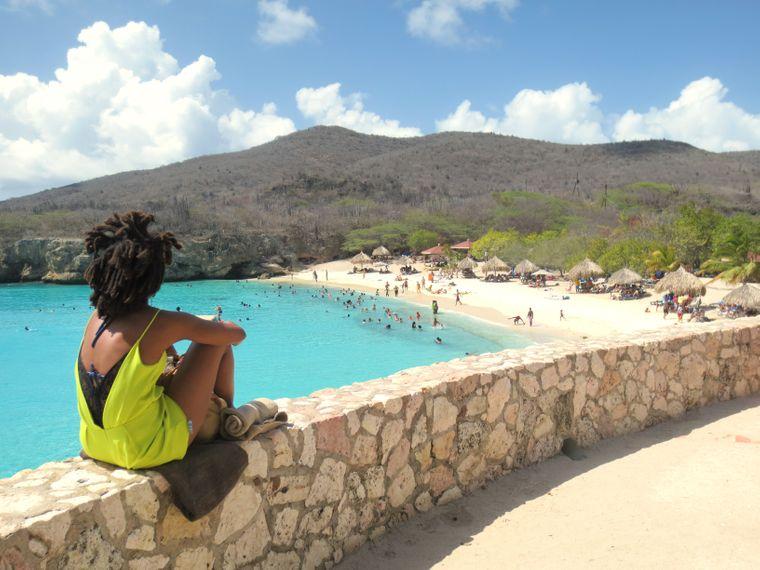 Eine Frau schaut auf den Strand Playa Kenepa auf Curaçao.