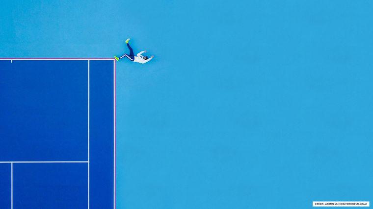 Ein Mann liegt an der Ecke eines Tennisfelds.