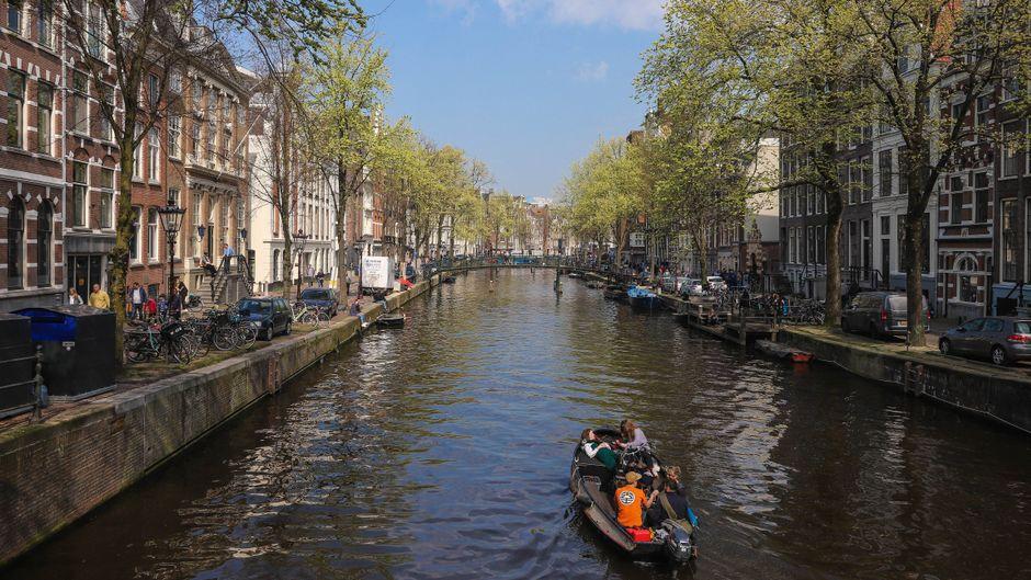 Ein Boot fährt auf einem Kanal in Amsterdam.